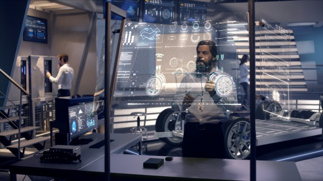 Engineers analyzing futuristic car chassis with digital screens.