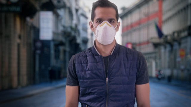 Isolated Man Wearing Protection Face Mask against Coronavirus Covid-19 Standing Still with Empty Streets on the Background. Dramatic impact of Pandemic Virus.