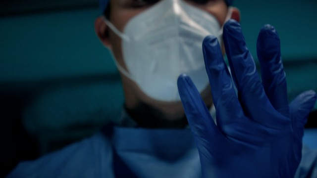 Cinematic Slow-motion of Male Surgeon Doctor Putting On Protective Medical Blue Surgical Gloves in Hospital.