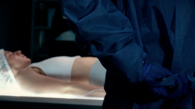 Cinematic Slow-motion of Surgeon Putting On Protective Medical Gown in Surgery Room using Hands.