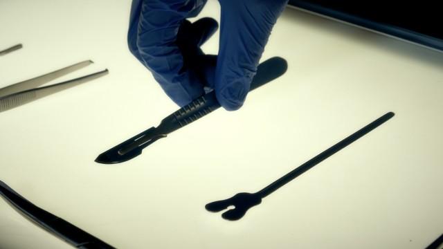 Cinematic Macro Shot of Doctor's Hand Grabbing Medical Scalpel. Close Up Shot of Medical Tools.