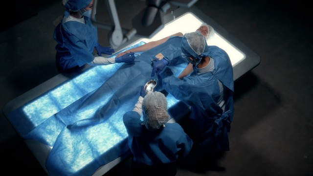 Elevated Shot of Team of surgeons perform a delicate operation using futuristic medical bed with light. Modern medical equipment.