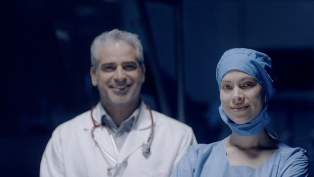Male and Female Doctor smiling to the camera.