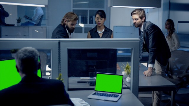 Diverse team of professionals working late at night watching data on computer.