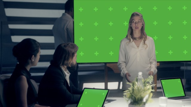 Mockup of Corporate Meeting Room: Professional Female Entrepreneur delivers a Business Pitch to Clients and Partners on a Chroma Green Screen Monitor with Trackers. Shot on ARRI ALEXA Mini UHD Camera