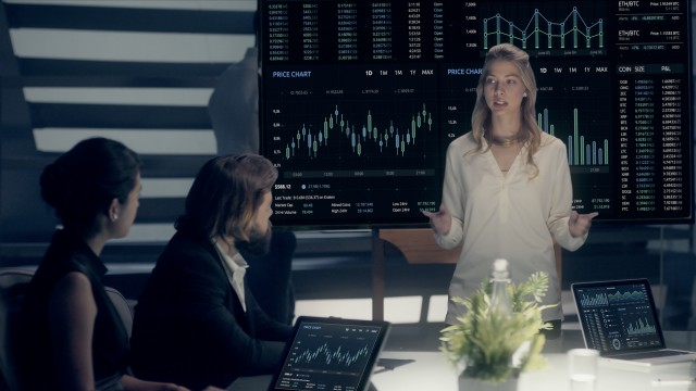 Corporate Meeting Room: Professional Female Executive presents Company Positive Results to Clients and Partners  on a large Monitor with Graphs and Charts. Shot on ARRI ALEXA Mini UHD Camera.