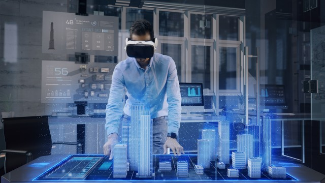 Professional Male Architect wearing Augmented Reality Headset makes gestures and redesigns 3D City Model.