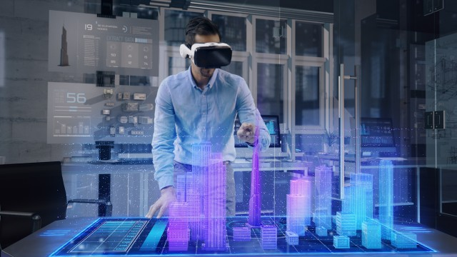 Professional Male Architect wearing Augmented Reality Glasses makes gestures and redesigns 3D City Model.