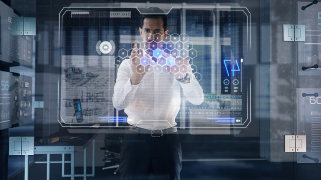 Successful Businessman works on large Transparent Interactive Window Touchscreen in his office.