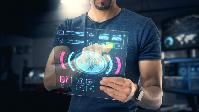 Close up of Independent and Young Male Robotic Design Engineer using aFuturistic Touchscreen Tablet with 3d infographics.