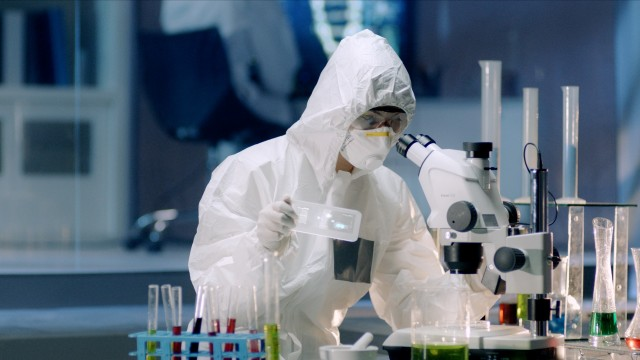 In the Secure High Level Laboratory Scientists in a Coverall Conducting a Research. Chemist analyzes a new virus on a digital screen and then Examines It Under Microscope.