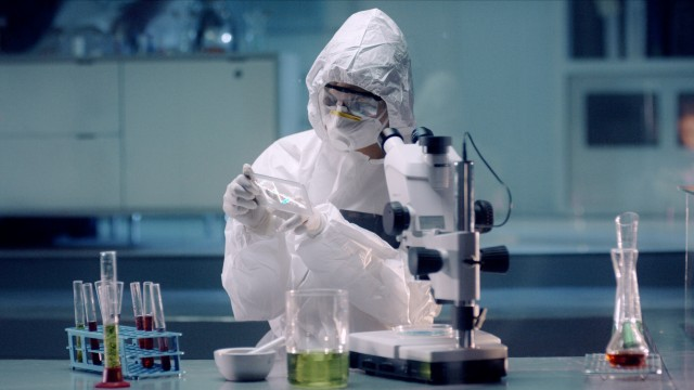 In the Secure High Level Laboratory Scientists in a Coverall Conducting a Research. Chemist analyzes DNA on a digital screen and then Examines It Under Microscope.