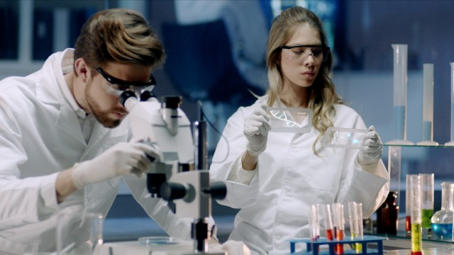 In the Secure High Level Laboratory Scientists in a Coverall Conducting a Research. Scientists analyze DNA on a digital screen and then Examines It Under Microscope.