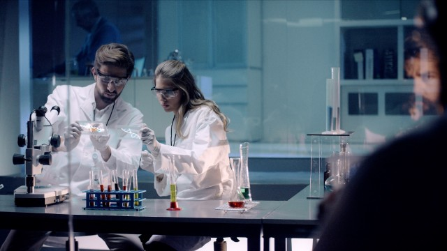 Team of Medical Research Scientists compare DNA Strand Molecule as they work on Genetic Engineering with Transparent Glass Displays.