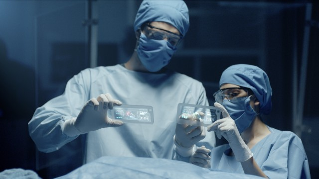 Professional Surgeon and Assistant Analyze Patient Lung Diagnosis Data on Transparent Devices During Surgery. Modern Hospital Operating Room. Shot on RED Epic-W Helium Camera.