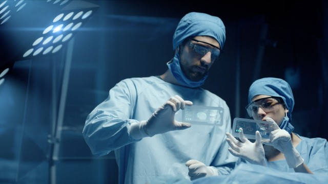 Professional Surgeon and Assistant Analyze Patient Diagnosis Data on Transparent Phones During Surgery. Modern Hospital Operating Room. Shot on RED Epic-W Helium Camera.