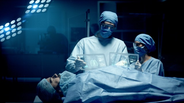 Professional Surgeon and Assistant Analyze Patient Lung Diagnosis Data on Transparent Tablets During Surgery. Modern Hospital Operating Room. Shot on RED Epic-W Helium Camera.
