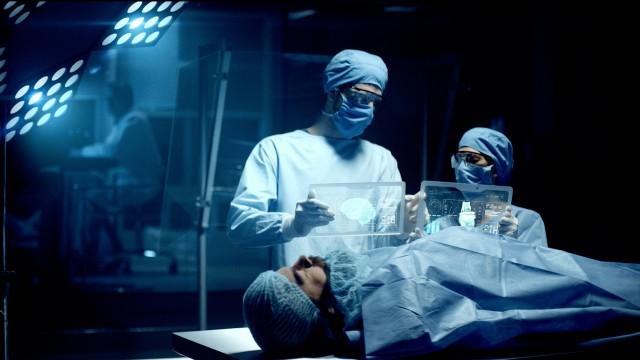 Professional Surgeon and Assistant Analyze Patient Brain Diagnosis Data on Transparent Tablets During Surgery. Modern Hospital Operating Room. Shot on RED Epic-W Helium Camera.