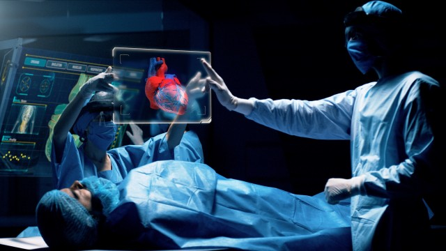 Group of surgeons using augmented reality holographic holo lens headsets interacting with a virtual interface showing patient organs. Doctor analyses HEART. Shot on RED Epic W Helium 8K Cinema Camera.