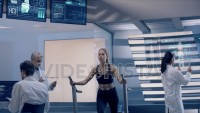 In Science High-Tech Sports Lab Beautiful Athlete Woman walks on treadmill using electrodes attached to her body. Futuristic Screens showing ECG and Medical Data Activity. Shot on Red Epic-W Helium