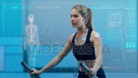 In Science High-Tech Sports Lab Beautiful Athlete Woman walks on treadmill using electrodes attached to her body. ECG and Holographic Data Overlay. Slow Motion. Shot on ARRI ALEXA Mini UHD Camera.