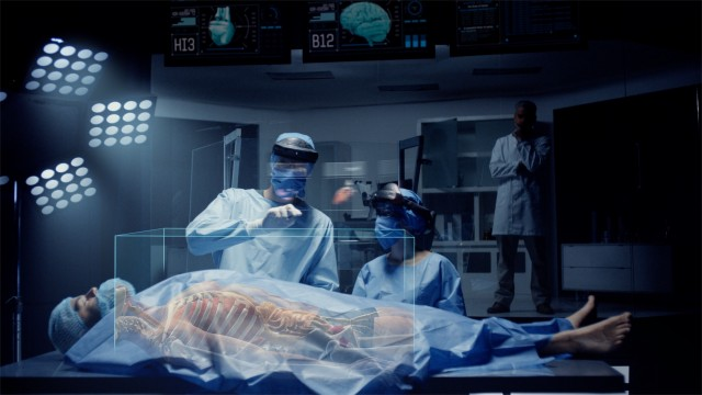 Team of Medical Surgeons use Augmented Holographic Technology to examine Patient. Nurse uses Hand Gestures to show the Organs, Bones and Full Anatomy of the Body of a Male Patient. Shot on RED Epic W.