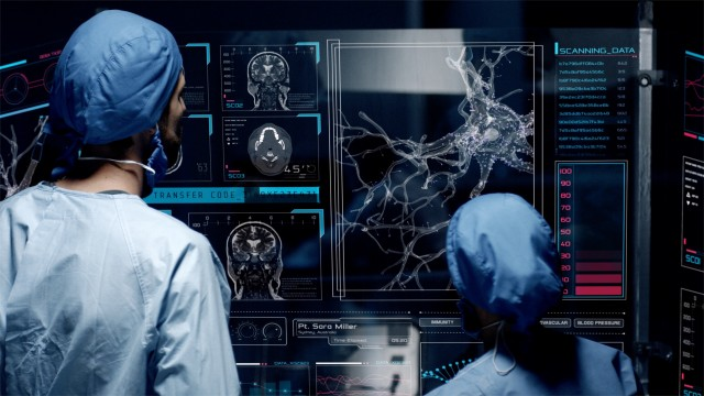 Professional doctors analyzing patient's medical MRI diagnosis by checking on a large glass screen with futuristic holograms. Concept of: medicine, doctors, future, holographic, brain scan