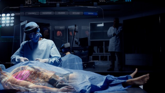 Team of Medical Surgeons use Augmented Holographic Technology to examine Patient. Doctors wear Holo Lens to view Organs, Bones and Full Anatomy of the Body of a Male Patient. Shot on RED Epic W.
