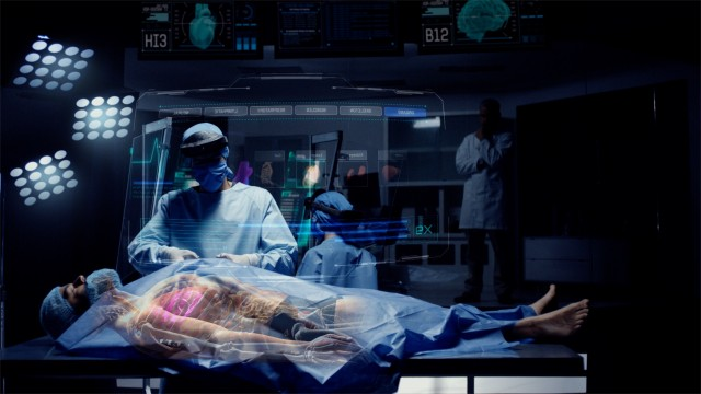 Team of Medical Surgeons use Futuristic Holographic Touchscreen Tablets to Examine Patient during Medical Procedure. Transparent Screens showing ECG and Medical Data Activity. Shot on RED Epic W.