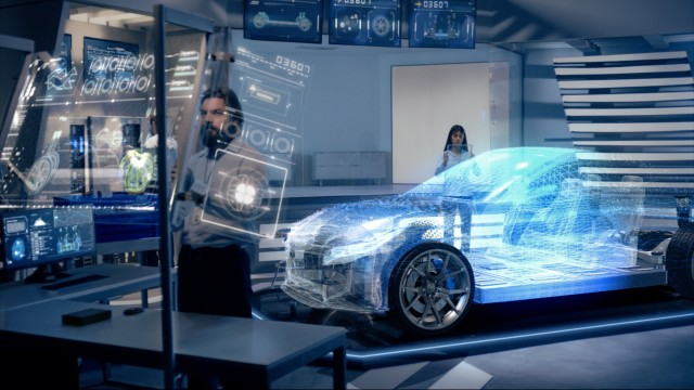 Engineers analyzing futuristic holographic car with digital screens.