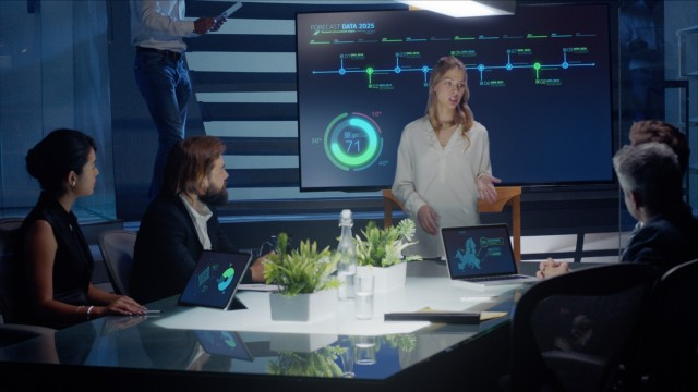 Female executive talks to board of directors and investors using a digital interactive monitor for presentation with green elements.