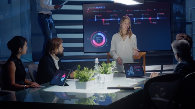 Female executive talks to board of directors and investors using a digital interactive monitor for presentation with purple and blue elements.