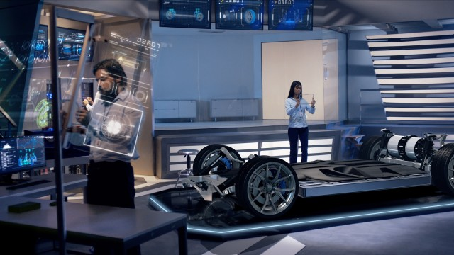 Engineers analyzing futuristic car chassis through a digital screen.