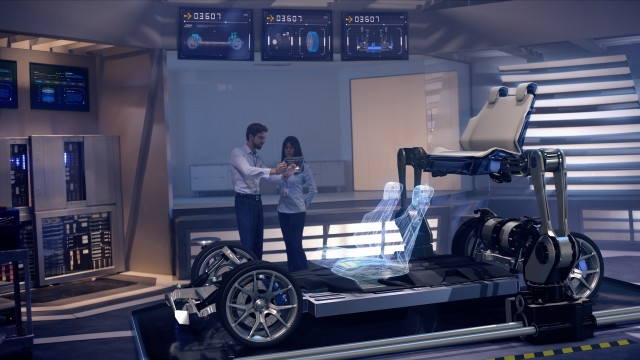 Engineers analyzing futuristic reinforced chassis and futuristic robotic arms placing car seats with digital screens.