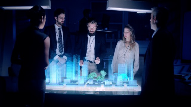 Professional Male Architect makes gestures and redesigns 3D City Model in front of boardroom.