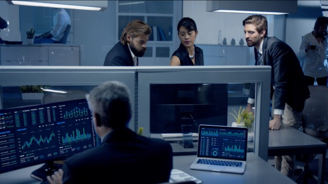 Diverse team of professionals working late at night discussing stock data on computer.
