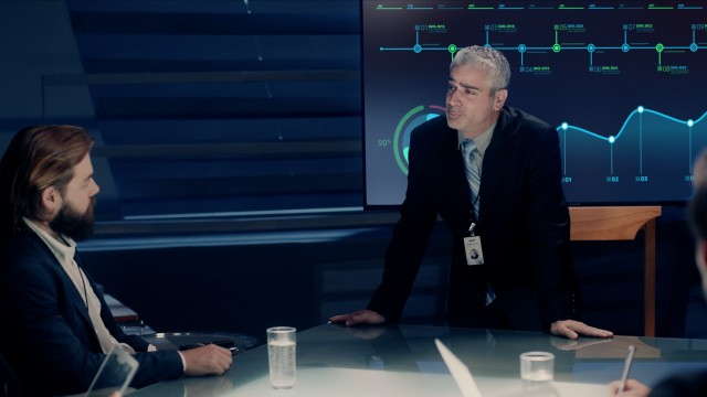 Corporate Meeting Room: Executive Director in Suit presents Forecast of Company to a Board of Executives and Business People with Graphs and Charts on a big Monitor. Shot on ARRI ALEXA Mini UHD Camera