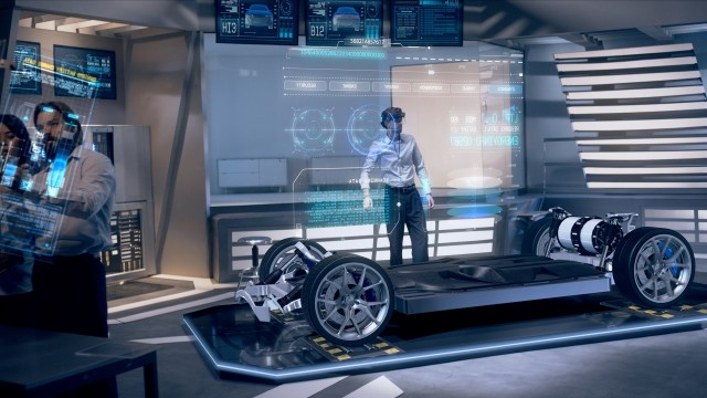 Automotive Engineers Analyzing Design and Performance of Electric Car Prototype using Augmented Holographic Technology and Futuristic Screens. High-tech Industrial Facility. Shot on RED Epic W Helium.