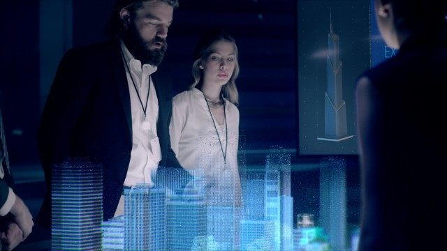 In the Near Future: Businessman in Suit presenting Architectural Project to Colleagues and Partners Standing around Futuristic Table with Holographic Modern Augmented Reality Technology.
