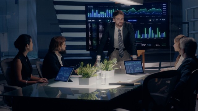 Corporate Meeting Room: Professional Male Executive presents Company Positive Results to Clients and Partners  on a large Monitor with Graphs and Charts. Shot on ARRI ALEXA Mini UHD Camera.