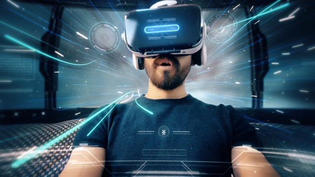 Bearded man uses VR-headset display for virtual reality game while entering an immersive holographic experience with infographics in UHD 4K. Concept of virtual hologram, simulation, gaming.