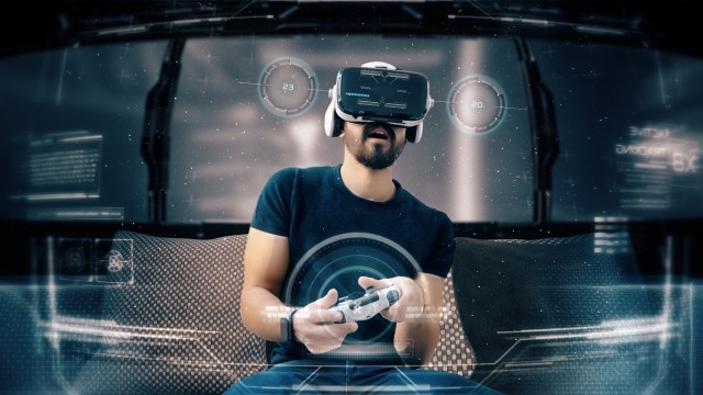Young man playing a video game wearing a VR-headset. Concept of virtual hologram, simulation, gaming.