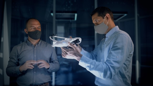 Close Up of Professional Engineers and Designers Wearing Protective Face Masks Work with a Futuristic Concept Face Mask Prototype Model.