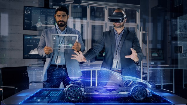 Male Automotive Designers in Suit Wearing AR Headset and Transparent Tablet Analyzing 3D Electric Concept Car Model.