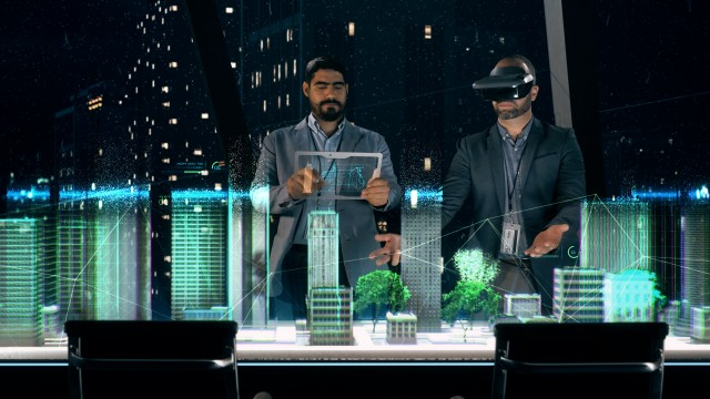 In the Near Future: Professional Designer in Suit wearing AR Headset presenting Architecture Project to Partner.