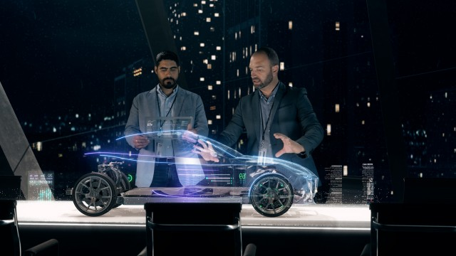 Automotive engineers working on design of Detailed Electric Car Chassis using futuristic transparent screens and AR Holographic Surface High Tech Table.